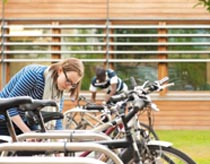 Female student securing her bike on the University campus