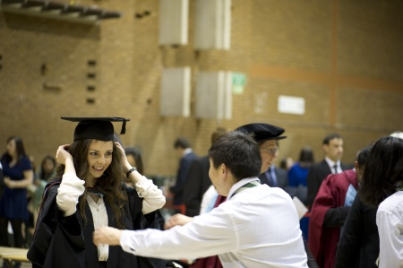 Graduand being helped putting her robe on