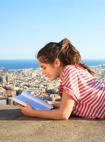 Woman reading book overlooking city