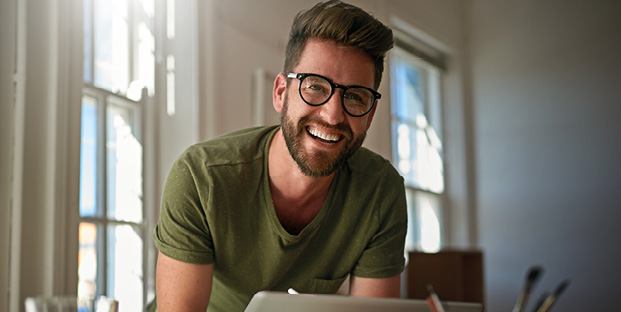 Man in t-shirt with glasses laughing in front of a computer screen