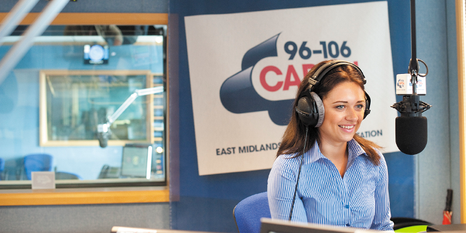 Female smiling and talking into a microphone in the Capital FM radio office