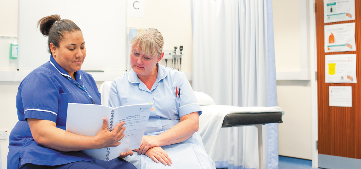 A nurse and student nurse looking at a document