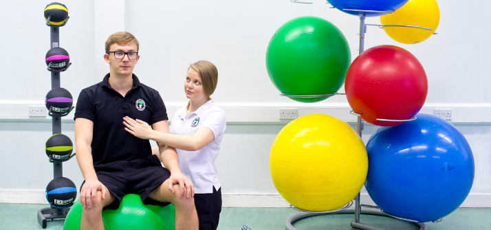Two students performing an examination using exercise balls