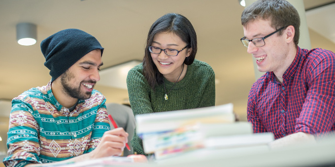 Postgraduate students smiling over a pile of books
