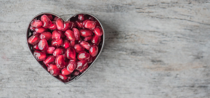 Heart shaped bowl of pomegranate seeds