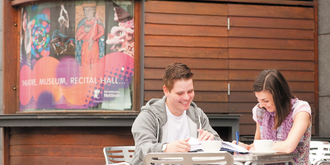 A woman and a man smiling while working together with an advert for Lakeside Arts gallery in the background