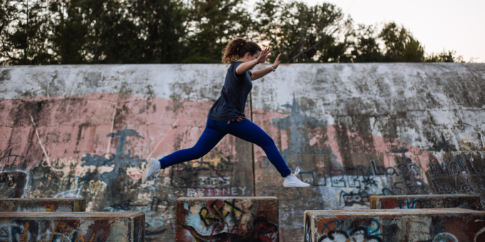 Young woman leaping over a gap