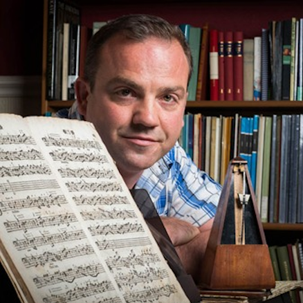 Portrait of Nick Baragwanath smiling at camera with sheet music and metronome