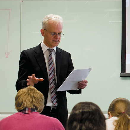 Richard Bell standing in front of students reading lecture notes