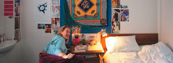 Female undergraduate student laughing in Florence Boot halls of residence bedroom 340x124