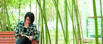 Female student sitting on bench next to bamboo, Ningbo campus