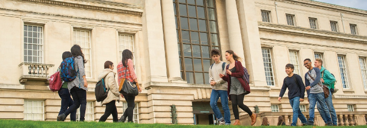 Undergraduate students walking and relaxing outside Portland building 714x249