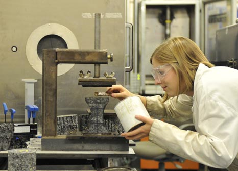 Female civil engineering student works on an experiment in a lab.