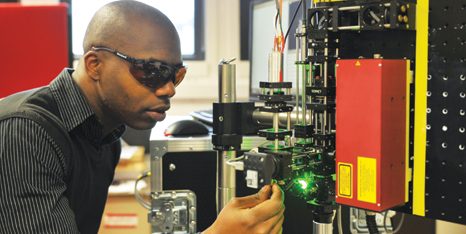 Male PhD student using a laser for an experiment.