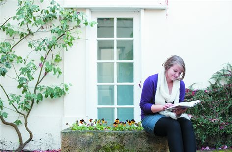 female student reading outside