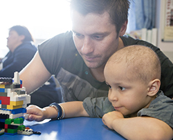 A young girl playing with lego with her dad at the Children's Brain Tumour Research Centre