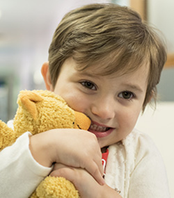 Olivia, a young patient at the CBTRC, clutches her teddy bear.