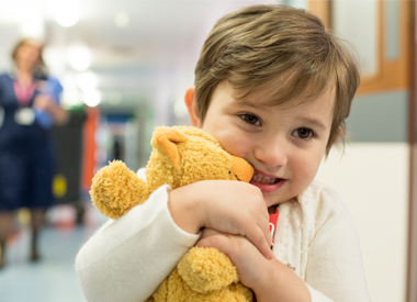 Young CBTRC patient Olivia clutching her teddy bear