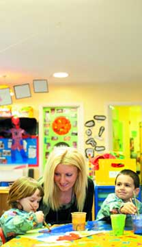 Nursery assistant working with children at the day nursery