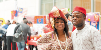 An African couple in brightly coloured dress stand together smiling at the camera