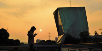 A silouetted youth stands in front a a futuristic building in China while looking at her mobile phone