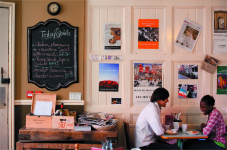 A couple sit in a european style cafe drinking coffee with posters of continental destinations adorning the walls
