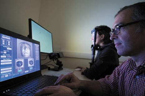 A researcher sits at a laptop monitoring an eye-tracking experiment while the participant is undergoing a test