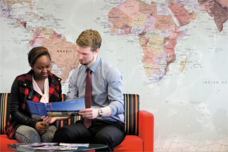 A smartly dressed man in a tie in discussion with an African lady, in front of a large wall print map of the globe