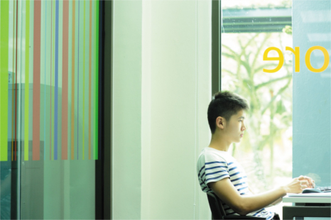 An asian student sits at a desk with his laptop, in front of a large window