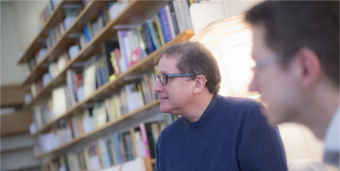 Two bespectacled men sit in front of a wall of neatly shelved books taking part in a discussion