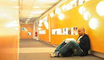 Male student reading in Hallward Library corridor