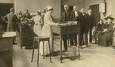 Photograph from 1912 showing nurses, doctors and patients in the Outpatients Consulting Room