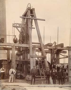 Photograph showing a large wooden-frame pump mechanism, surrounded by workmen