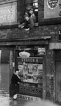 Photograph of a basket being lowered from the upstairs window of a flooded house; dated 1947; The Meadows, Nottingham