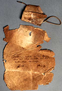 A bundle cover, discoloured and much damaged around the edges, and the parchment tag that was used to attach the pages.