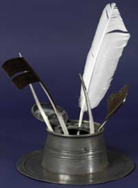 Photograph of some quill pens standing in an inkwell