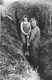 Photo of two land army girls, in overalls, digging a ditch.