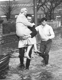 Photograph of a woman being carried through flood waters, Main Street, Bulwell, 4 December 1960 (RE/DOP/H2/25). Courtesy of the Nottingham Post Group
