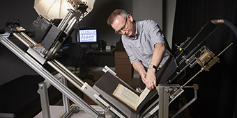 Manuscripts and Special Collections staff member using the book cradle