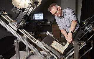 Mark Bentley photographing a book  using the preservation book cradle