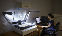 Manuscripts and Special Collections staff member using the flatbed scanner