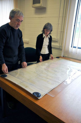 Placing a polyester protective sheet over a large map