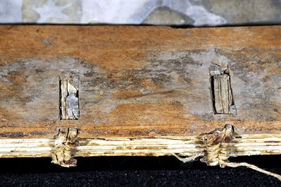 Cords threaded inside wooden board, prayer book WLC/LM/11 before conservation