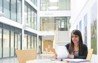 student studying in the atrium of mathematical sciences building