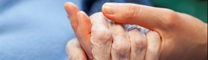 Carer holding hand of elderly patient