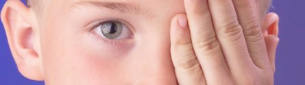 Young boy covering his eye with his hand