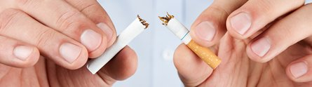 Man's hands breaking a cigarette in half