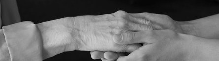 Hands of a young woman holding an elderly lady's hand