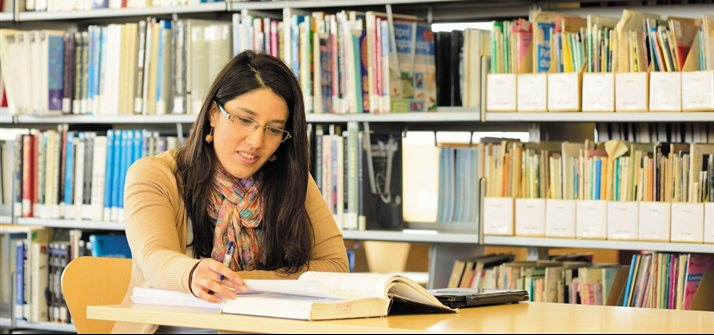 Female postgraduate studying in library