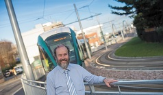 Sustainable Transportation and Electrical Power Systems - Assistant Professor Dr Nick Thom standing in front of a tram - Engineering (15213)